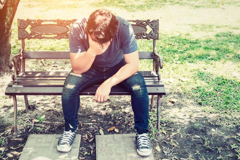 sad man sitting on bench outside